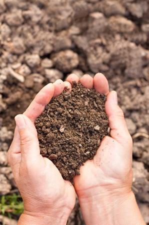 tierra fertil: Manos femeninas llenos de suelo sobre fondo de suelo.Que representa la fertilidad