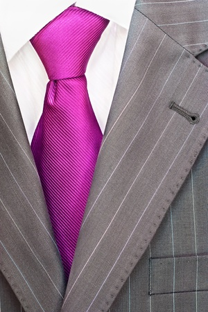 Detail of a mens striped business suit.Pink tie and a shirt