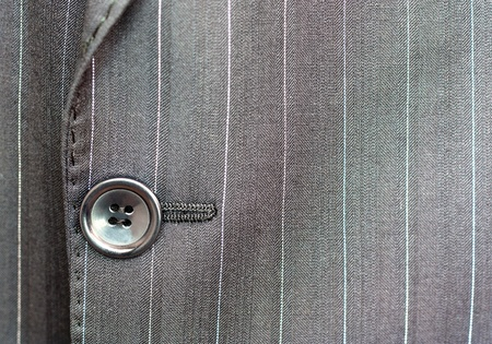 tailor: Close up of a button on a pin striped business suit coat
