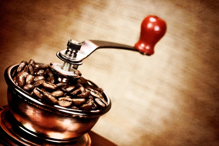 Contrast image of vintage  coffee  mill or grinder with coffee beans .Dramatic lightning photo