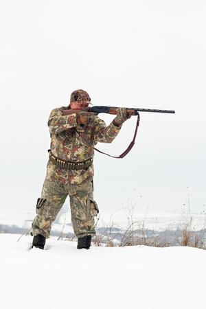 fusil de chasse: Homme en tenue de camouflage chasseur visant sa cible ou proie avec sa scène gun.Winter
