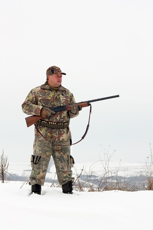 Male hunter in camouflage,holding his gun and looking for his target or prey .Winter scene photo