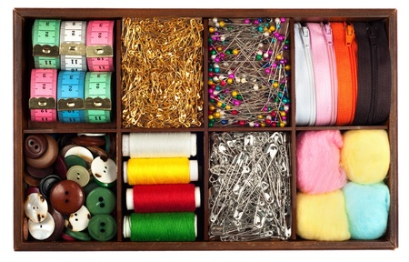 kit de costura: Surtido de materiales de confección diferentes cinta métrica-, alfileres, agujas, cremalleras, botones, spivels, hilos y algodones en caja de madera de época o retro aislado sobre fondo blanco