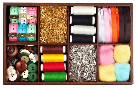 Assortment of different   tailoring materials  tape-measure,safety pins,needles,zippers,buttons,spivels,threads and cottons   in vintage or retro wooden box isolated on white background photo