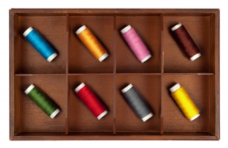 Collection of different color spools of thread  in a grunge wooden box Isolated on white background photo