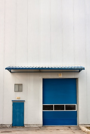 Industrial Warehouse Unit with blue  roller shutter door Copy space