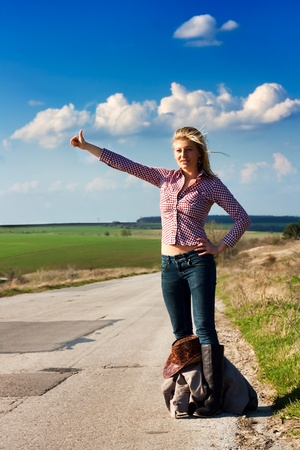 Pretty young Travel  woman hitchhiking along an empty  country road with sun shinning in her face
