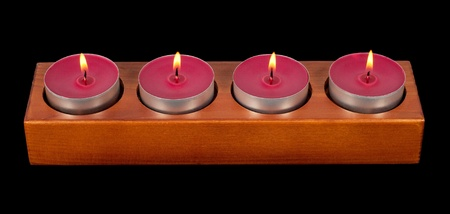 Wooden candleholder or candlestick with four burning or flaming  candles isolated on black  background photo