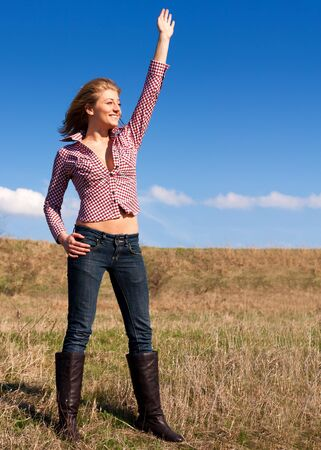 Pretty,sexy  woman waving hand at someone outdoors photo