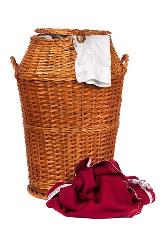 Wicker laundry basket or Hamper full with dirty clothes  over white background photo