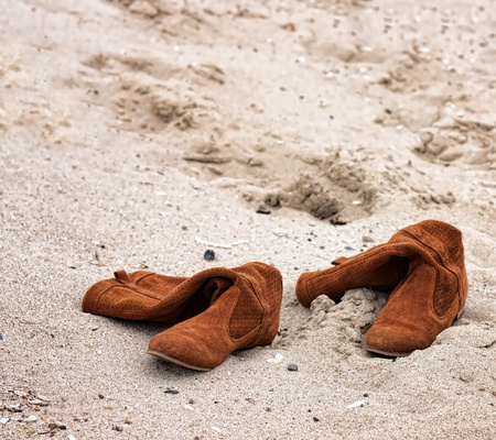 Woman boots abandoned on sandy beach photo
