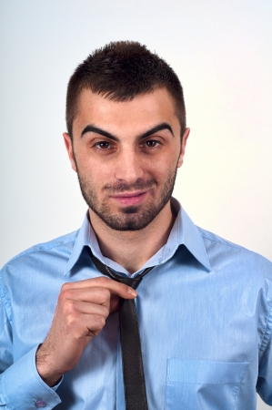 Portrait of a handsom young businessman with casual tie posing in studio photo