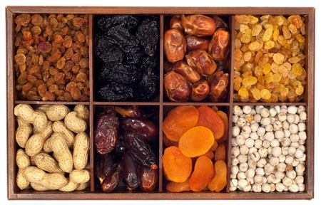 Assorted dried fruits in wooden box,isolated on white background Raisin,prune,date,monkey-nut, apricot,nuts photo