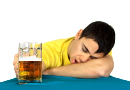 Drunk man sleeping at the pub table with a glass of cold, light beer Isolated on white background photo
