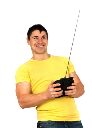 flying man: Young athletic man holding a radio remote control (controlling handset) for helicopter or plane.Isolated on white background