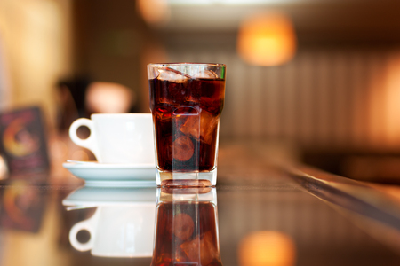 caffeine: A glass of cola or soda with ice cubes and cup of black coffee on the bar