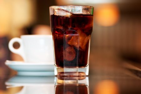 A glass of cola or soda with ice cubes and cup of black coffee on the bar