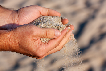 sand grains: Man Hands holding and spilling sand on the beach.Very shallow depth-of-field and motion blur.