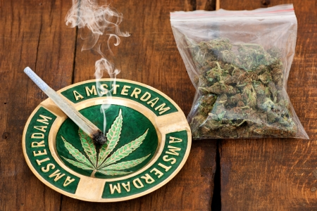 Smoking Marijuana Joint in an ashtray with amsterdam sign  and a big plastic bag of weed on wooden background Stockfoto