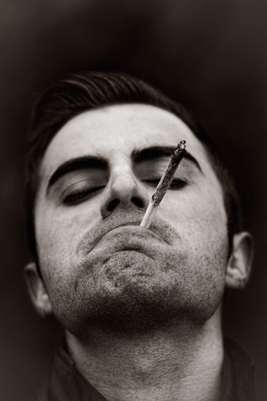 Black and white portrait of young man with closed eyes enjoying his marijuana or joint photo