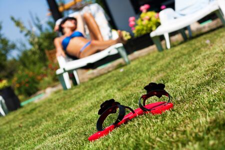 Blured image of sexy young woman making sunbaths on a beautiful day in the garden photo