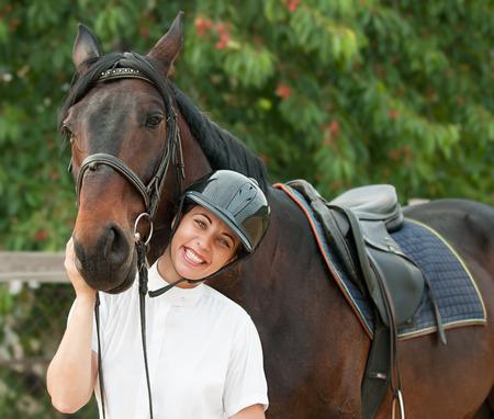 uomo a cavallo: Allegra giovane donna fantino con cavallo di razza all'aperto