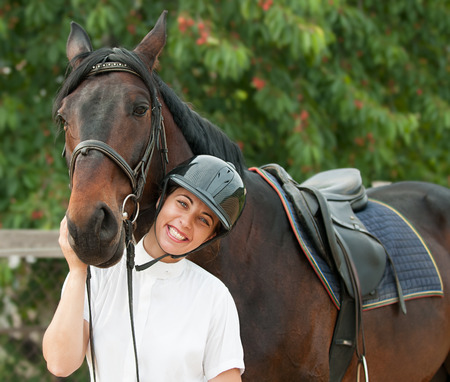 Cheerful young jockey woman  with purebred horse outdoors