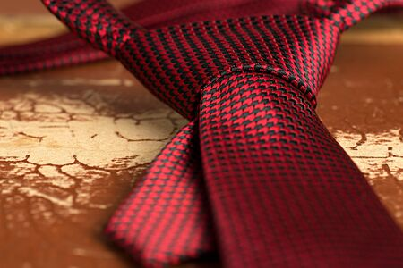 collo: Legame rosso con Windsor nodo su un vecchio grunge valigia come background.Shallow DOF