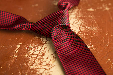 windsor: Red tie with Windsor knot on a old grunge suitcase as a background.Shallow DOF