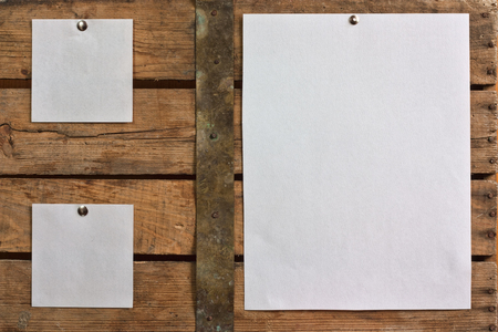 Three  pieces of blank paper tacked to wooden background.Ready for your text