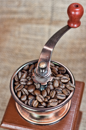 Contrast image of vintage  coffee  mill or grinder with coffee beans .Dramatic lightning