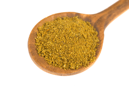 Curry powder  on wooden spoon  isolated on white background  Stock fotó