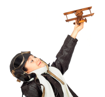 Happy cute boy dressed like a World War II pilot playing with wooden airplane toy isolated on white background.Vintage look Stockfoto