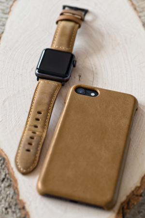 Generic design smartwatch and smartphone with genuine leather case and strap on wooden background.Shallow DOF