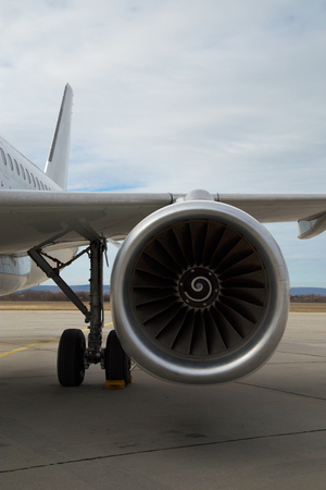 Front view of a big commercial and passenger airplane engine reactor in an airport.Rotating fan and turbine blades