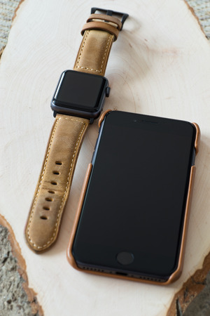 Generic design smartwatch and smartphone with genuine leather case and strap on wooden background. Shallow DOF