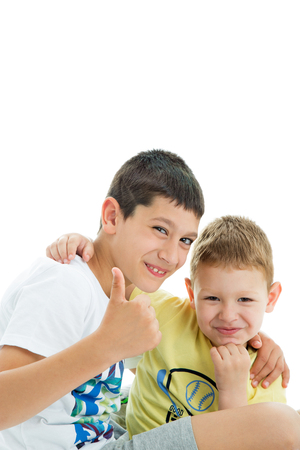 Two happy joyful and loving  brothers isolated on white background.Smilling at camera.Thumbs up.Four years and nine years old Stockfoto
