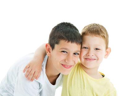 Dos hermanos felices y cariñosos alegres aislados sobre fondo blanco. Sonriendo a la cámara.