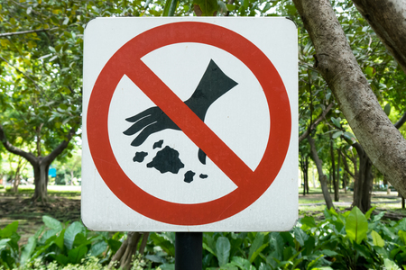 littering: Please Keep Area Clean the sign dont drop waste, no littering in the park in plants background Stock Photo