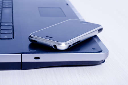 The mobile phone lies on the laptop Stock Photo