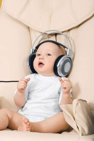 The child sits and listens to music in ear-phones Stock Photo - 6635695