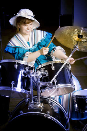 The young woman plays drums photo