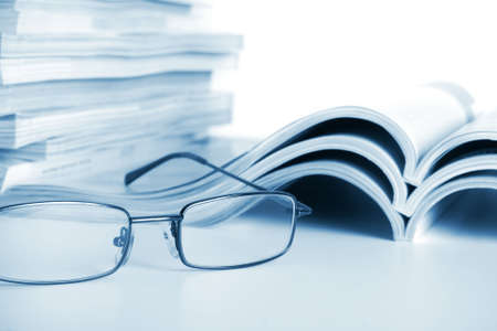 Open journals with glasses in front