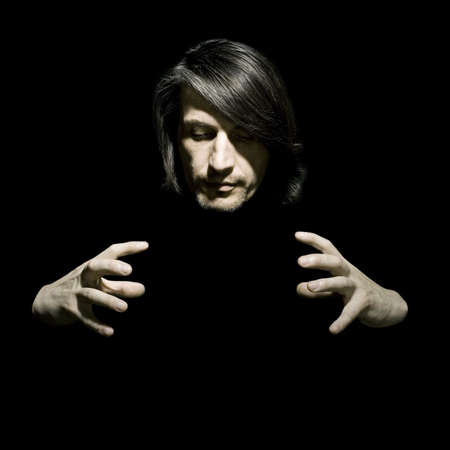 telepathy: Portrait of the man of the illusionist on a black background