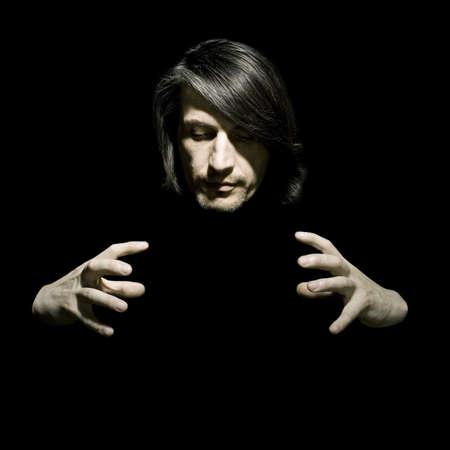 Retrato del hombre del ilusionista sobre un fondo negro