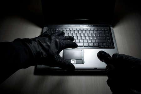 ladrones: El hacker intenta romper el sistema en el equipo port�til  Foto de archivo