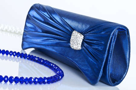 Ladies handbag and beads on a white background