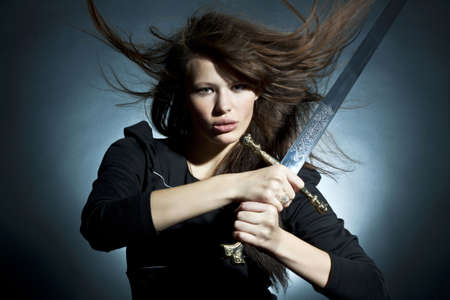 The beautiful young woman holds a sword in a hand Stock Photo - 8153768