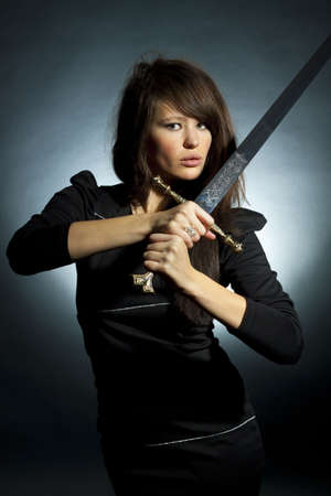 The beautiful young woman holds a sword in a hand
