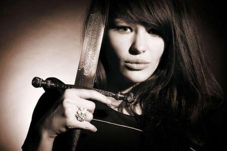 warrior sword: The beautiful young woman holds a sword in a hand